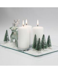 Juldekoration med ljus, renar, granar och snö på glasfat