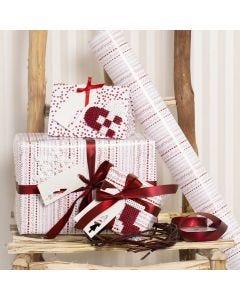 Julklappsinslagning i rött och vitt, dekorerade med julmotiv av rörpärlor.