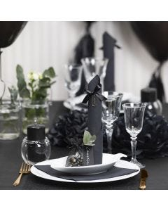 Bordsdukning och bordsdekoration i svart med pappersblommor, ballonger, servetter vikta som torn och bordskort.