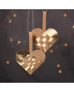 Flätade julhjärtan av läderpapper i natur och guldfärger.