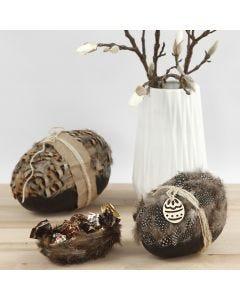 Tvådelade påskägg dekorerade med naturfjädrar, kartong och naturhampa.
