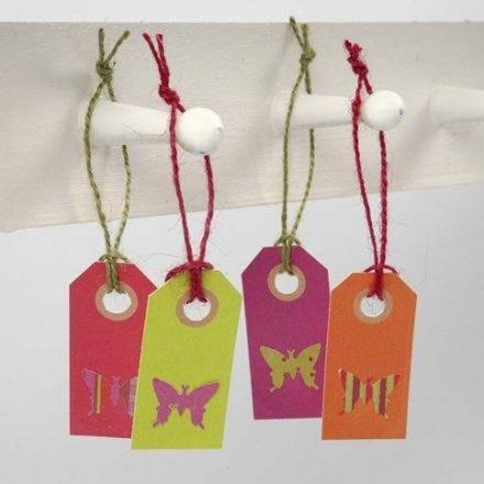 Utstansade fjärilar i designpapper på manillamärken