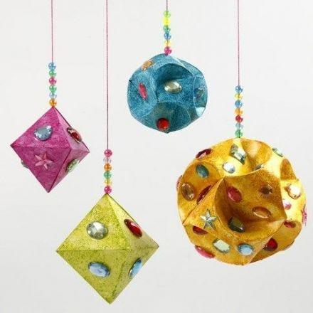 Rhinstenar och glitterfärg på prismor och kulor av papper