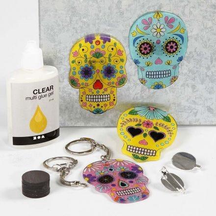Berlocker, magneter och broscher av målade, förtryckta motiv på krympplast.