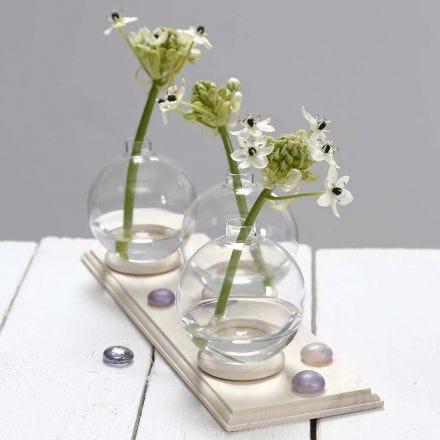 Liten vas av glaskulor stående på gardinring