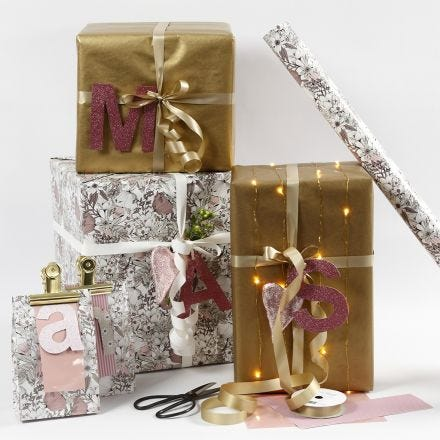 Presentinslagning i rosa och guld med bokstäver