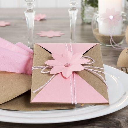 En inslagen inbjudan med snöre och utstansad blomma