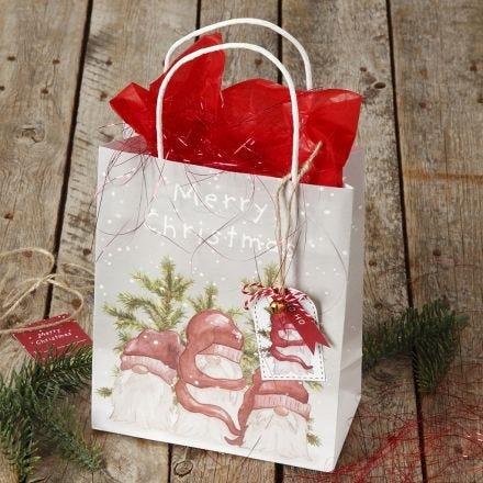 Julklappsinslagning med presentpåse och presentetikett med bjällra