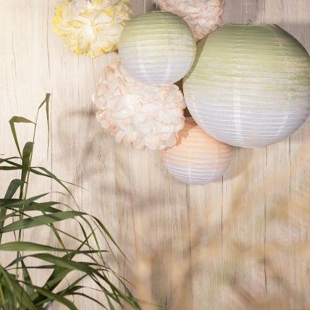 Festdekoration av rispapperslampor och papperspompomer målade med hobbyfärg