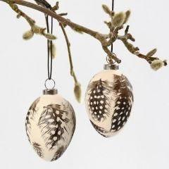 Ägg av terrakotta med pärlhönsfjädrar
