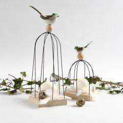 Fågel på fågelbur av metalltrådar på träikon