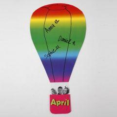 Luftballong av regnbågskartong med korg av vågpapp