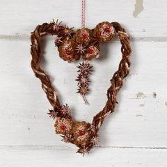 Flätad grenkrans i hjärtform med kottar och anisstjärnor