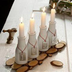 Adventsljusstakar av mjölkflaskor med numrerade tags av zink