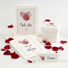 Bröllopsinbjudning och dekorationer med hjärta av fingertryck