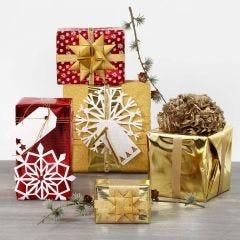 Paketinslagning med metallpapper och glittriga dekorationer.