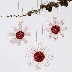 Dekorationer av stjärnstrimlor i vellumpapper med rosett i mitten och glitter