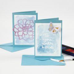 Kort och bordskort med text av ritgummi som målats över med akvarellfärg.