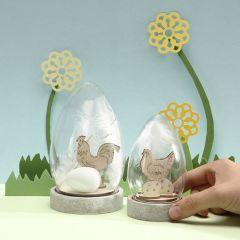 Kupa dekorerad med påskfigurer i trä, ägg och vita fjädrar.