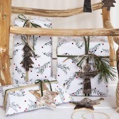 Julklappsinslagning med gröna grenar som motiv, dekorerade med snöre, band och presentetikett av bark.