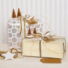 Julklappsinslagning i guld med glittriga dekorationer.