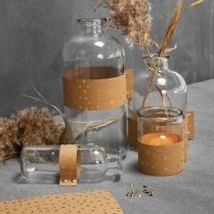 Glasflaskor och ljusglas dekorerad med läderpapper.