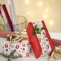 Kreativ julklappsinslagning med två typer av presentpapper och en träfigur.