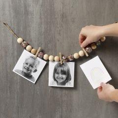 Bilder på snöre med träpärlor, klädnypor och paljetter.