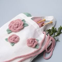 Textilkasse dekorerad med rosor gjord av stickade tuber
