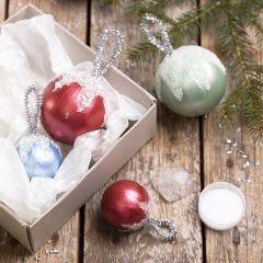 Julkulor dekorerade med metallfärg och konstgjord snö