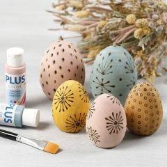 Målade ägg av trä dekorerade med en brännpenna