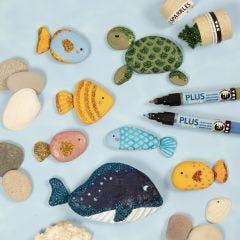 Havsdjur målade på sten med tusch och dekorerade med bio-glimmer