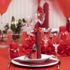 Bordsdukning och bordsdekoration i röd med pappersblommor, ballonger, servetter vikta som torn och bordskort.