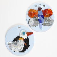 Mosaikfigurer på runda plattor av terrakotta