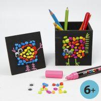 Svartmålade pennskrin och collageramar med mosaik och grafik