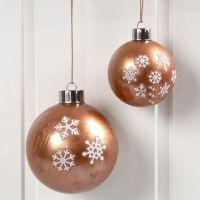 Julgranskulor med kopparfärg på insidan och stickers på utsidan