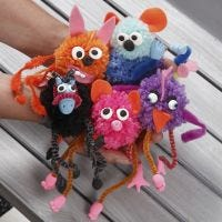 Fantasidjur av pompomer och piprensare, dekorerade med filt och Silk Clay.
