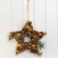 Stjärna av metall till dörrdekoration, dekorerad med kottar, metallull m.m.