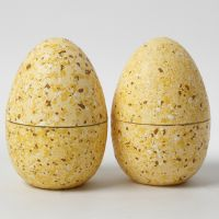 Tvådelade ägg dekorerade med terrazzoflakes och hobbyfärg.