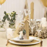 Bordsdukning och bordsdekoration i guld med pappersblommor, ballonger, servetter vikta som torn och bordskort.