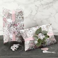 Presentaskar dekorerade med rosa band, metallring och blomsteretiketter