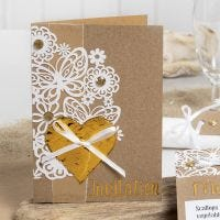 Inbjudningskort dekorerad med spetskartong, hjärta av dekorationsfolie och rhinestones.