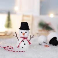 Nissen bygger en snögubbe framför sin nissedörr.