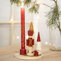 Ljusstake dekorerad med nötknäpparfigur, julgran och moniglaskulor.
