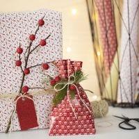 Julklappsinslagningar med grenar och konstgjorda bär.