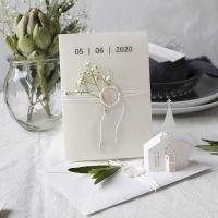 Inbjudan i råvita nyanser med utstansad kyrka och pergamentpapper
