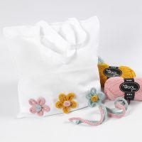 Textilkasse dekorerad med blommor gjorda av tubstickat.